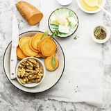 Ingredients for a healthy and comfortable diet: slices of fresh raw sweet potato, honey, walnuts, rosemary cheese, sage. Salt on a light background using a Stock Image