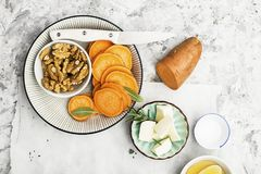 Ingredients for a healthy and comfortable diet: slices of fresh raw sweet potato, honey, walnuts, rosemary cheese, sage. Salt on a light background using a Royalty Free Stock Image