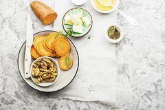 Ingredients for a healthy and comfortable diet: slices of fresh raw sweet potato, honey, walnuts, rosemary cheese, sage. Salt on a light background using a Stock Photos