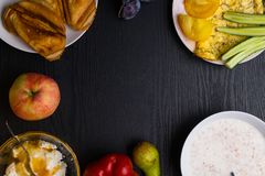Ingredients of healthy dietary food breakfast green leafs, tomatoes, pear, cottage cheese, omelette with dill, apple, pepper, porr. Idge, toasts, honey on wooden stock image