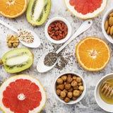 Ingredients of healthy dietary food breakfast pink grapefruit, orange, chia seeds, quinoa, green herbs, kiwi, wild rice. Almonds, walnuts, hazelnuts on a light Royalty Free Stock Photography