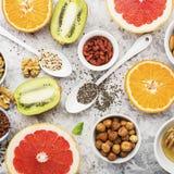 Ingredients of healthy dietary food breakfast pink grapefruit, orange, chia seeds, quinoa, green herbs, kiwi, wild rice. Almonds, walnuts, hazelnuts on a light Stock Photo