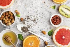 Ingredients of healthy dietary food breakfast pink grapefruit, orange, chia seeds, quinoa, green herbs, kiwi, wild rice. Almonds, walnuts, hazelnuts on a light Stock Image