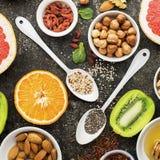 Ingredients of healthy dietary food breakfast pink grapefruit, orange, chia seeds, quinoa, green herbs, kiwi, wild rice. Almonds, walnuts, hazelnuts on a gray Stock Photos