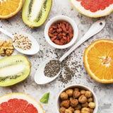 Ingredients of healthy dietary food breakfast pink grapefruit, orange, chia seeds, quinoa, green herbs, kiwi, wild rice. Almonds, walnuts, hazelnuts on a light Royalty Free Stock Images