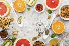 Ingredients of healthy dietary food breakfast pink grapefruit, orange, chia seeds, quinoa, green herbs, kiwi, wild rice. Almonds, walnuts, hazelnuts on a light Stock Photography