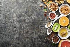 Ingredients of healthy dietary food breakfast pink grapefruit, orange, chia seeds, quinoa, green herbs, kiwi, wild rice. Almonds, walnuts, hazelnuts on a gray Royalty Free Stock Photo