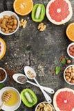 Ingredients of healthy dietary food breakfast pink grapefruit, orange, chia seeds, quinoa, green herbs, kiwi, wild rice. Almonds, walnuts, hazelnuts on a gray Royalty Free Stock Photography