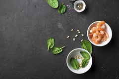 Ingredients healthy food: spinach, pine nuts, shrimp on a dark background. Top View. Stock Photography