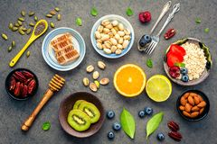 Ingredients for the healthy foods background Mixed nuts, honey,. Berries, fruits, blueberry, orange, almonds, oatmeal and chia seeds .The concept of healthy stock photo