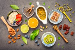 Ingredients for the healthy foods background Mixed nuts, honey,. Berries, fruits, blueberry, orange, almonds, oatmeal and chia seeds .The concept of healthy royalty free stock images
