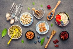 Ingredients for the healthy foods background Mixed nuts, honey,. Berries, fruits, blueberry, orange, almonds, oatmeal and chia seeds .The concept of healthy stock image