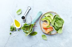 Ingredients for a healthy salad on gray stone background. Smoked salmon, avocado, spinach, sorrel, radis sprouts, black cumin. Flat lay. Healthy diet. Symbolic stock image