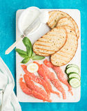 Ingredients for healthy sandwich. Grilled bread slices, smoked salmon, cottage cheese, cucumber and basil on white Stock Photography