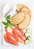 Ingredients for healthy sandwich. Grilled bread slices, smoked salmon, cottage cheese, cucumber nd basil on white wooden Stock Image