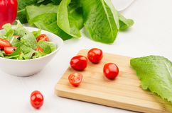 Ingredients for healthy vegetarian spring salad - fresh greens, tomatoes, pepper on cuttingboard on white wood background, close stock photography