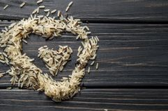 Ingredients. Heart shaped hill of wild rice on a wooden background. stock image