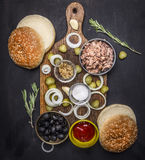 Ingredients for home kuking burger with tuna, pickled cucumbers, onions, olives sauce  cutting board wooden rustic back Stock Photography