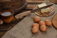 Ingredients for homemade bread over sackcloth and broun background, knife in butter. Ingredients for homemade bread over burlap and wooden broun background stock image