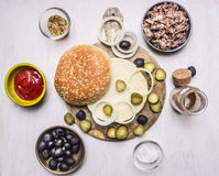 Ingredients for homemade burger, tuna, bun, sauce, olives, spices on wooden rustic background top view border, place text Royalty Free Stock Images