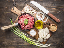 Ingredients for homemade burgers with onions and garlic, laid out on a chopping board a green onions  on wooden rustic backgr Stock Photo
