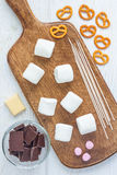Ingredients for homemade christmas sweetness: marshmallow, chocolate, pretzel, wooden sticks, top view Stock Photo