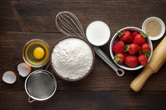 Ingredients for homemade strawberry cake or pie with fresh berries on wooden rustic background. Royalty Free Stock Photography