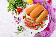 Ingredients for hot dog with sausage. bacon, cucumber, tomato and red onion. On white plate. Top view. Flat lay Stock Photos
