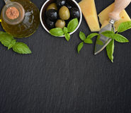 Ingredients of italian cuisine. Basil, parmesan, olives  and olive oil - on dark background Stock Photos