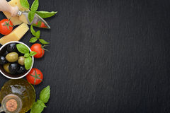Ingredients of italian cuisine. Cherry tomato, basil, parmesan, olives  and olive oil - on dark background Royalty Free Stock Photos
