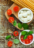 Ingredients of Italian cuisine - fresh basil, cherry tomatoes, b. Aby mozzarella, fresh pasta fusilli lunghi on old metal background top view stock images