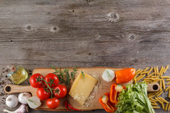 Ingredients for Italian dish. Parmesan cheese, pasta and fresh vegetables. On an old wooden background. Stock Photography