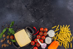 Ingredients for Italian dish. Parmesan cheese, pasta and fresh vegetables. On an old wooden background. Recipe royalty free stock images