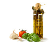 Ingredients for Italian food. A still life of ingredients for cooking Italian food. A bottle of olive oil, fresh garlic, basil and a tomato isolated on white stock photos
