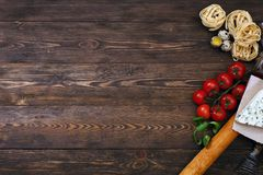 Ingredients for an Italian food recipe. Overhead view of ingredients for an Italian pasta recipe on rustic wood boards with copyspace Royalty Free Stock Photo