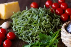 Ingredients for Italian green pasta. Wooden background stock photo