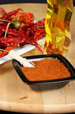 Ingredients for italian hot cuisine. Sun dried, red hot chilli peppers, chilli pepper powder and hot pepper oil. Shallow DOF Stock Image