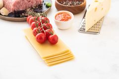 Ingredients for Italian lasagna with fresh cherry tomatoes and green basil leaves on sheets of dried pasta. Copy space. stock image