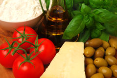 Ingredients for an Italian meal. Tomatoes, basil, olive oil, flour and parmesan cheese stock photo