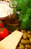 Ingredients for an Italian meal. Tomatoes, basil, olive oil, flour and parmesan cheese stock photography