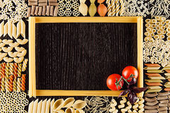Ingredients Italian pasta on dark brown wooden board with empty copy space as decorative frame background. Mock up restaurant menu Stock Image