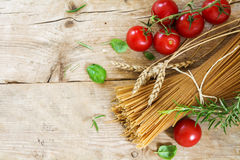 Ingredients for an Italian pasta meal with wholemeal spaghetti w. Heat ears, tomatoes and basil herbs as seen from above on a rustic wooden background, generous Royalty Free Stock Photos