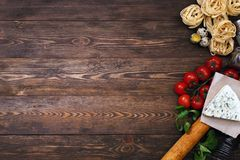Ingredients for an Italian pasta recipe on rustic wood. Overhead view of ingredients for an Italian pasta recipe on rustic wood background Royalty Free Stock Photography