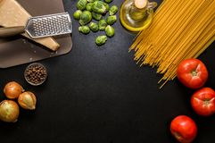 Ingredients for italian pasta. Spaghetti, tomatoes, oil, onion, parmezan on black wooden backg stock image