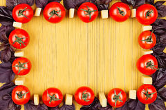 Ingredients Italian pasta top view - cherry tomatoes, basil, cheese on yellow surface spaghetti with empty copy space as decorati. Ve frame background. Mock up Stock Photography