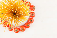 Ingredients Italian pasta top view - sheaf spaghetti, cherry tomatoes, basil, cheese on white wood board with empty copy space as. Decorative border background Royalty Free Stock Photos