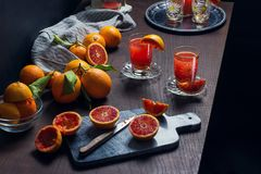Juicing Blood Oranges to Make Orange Juice. The ingredients and kitchen tools for making orange juice are on a wooden table in a dark kitchen. Sicilian blood Royalty Free Stock Photo