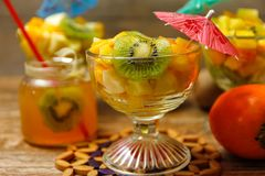 Cup of fresh fruit salad with different tropical fruit on a wooden table with raw fruits in the background stock image