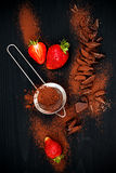 Ingredients for making chocolate brownies. Strawberries, chopped chocolate with cocoa over black wooden background, top view. Royalty Free Stock Photo