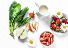 Ingredients for making coconut probiotic yogurt, spinach, apple, strawberry detox smoothie on a light background, top view royalty free stock photography
